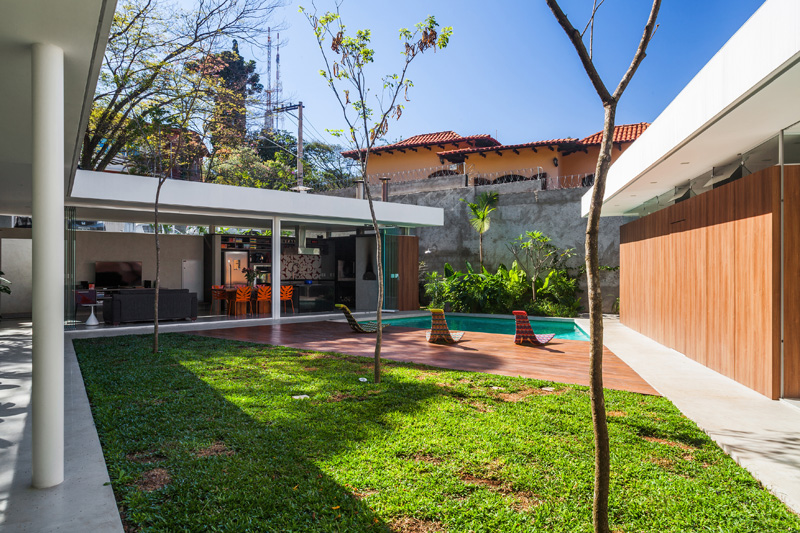 A home with glass walls and a central courtyard in brazil for Central courtyard home designs